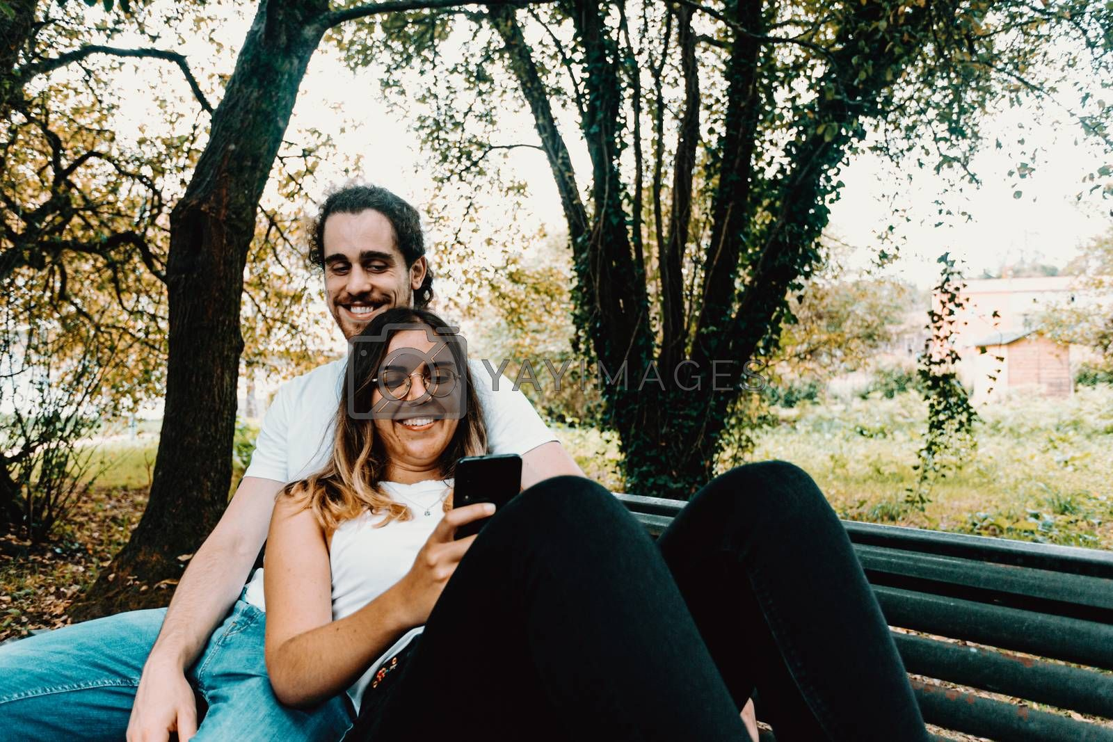 A young couple resting in a bench while looking the phone in the park