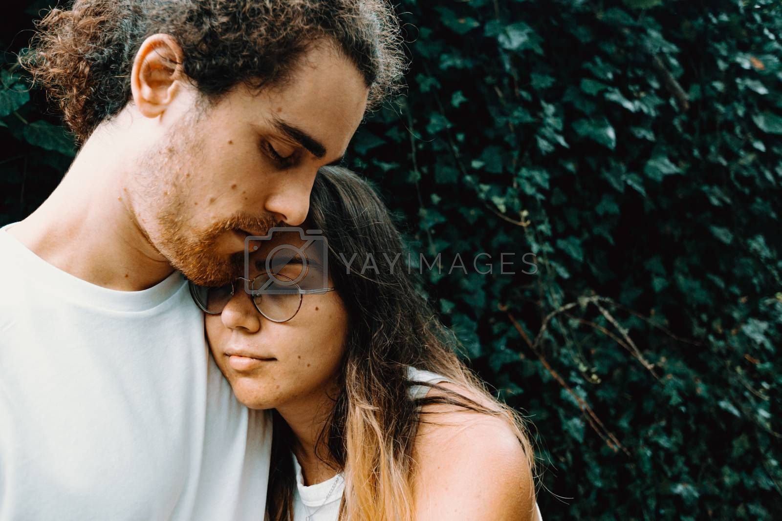 A young and natural spanish couple hugging each other in front of some leaves