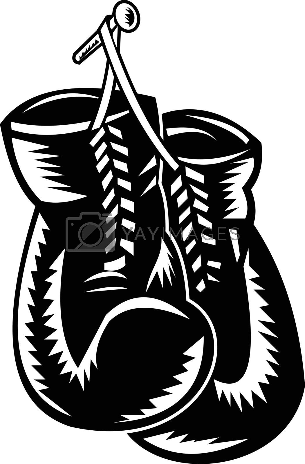 Retro woodcut style illustration of a pair of boxing gloves hanging on nail on isolated background done in black and white.