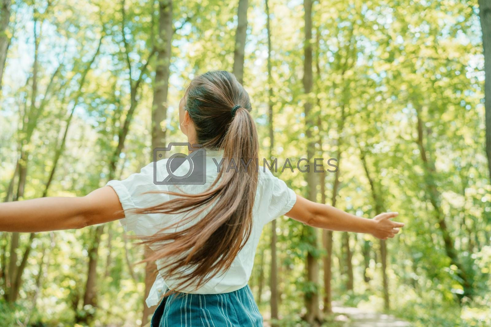 Happy woman in forest with open arms from behind breathing clean air. Environment, no pollution healthy natural living lifestyle. Free spirit in the woods.