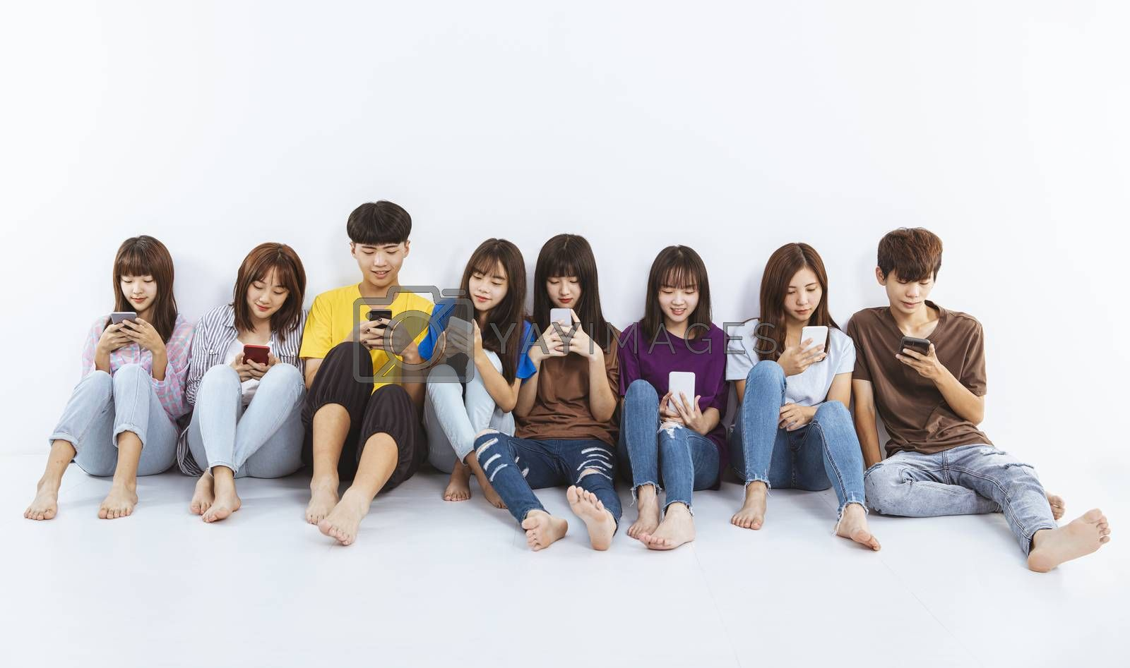 young group using smartphones and  sitting on the floor