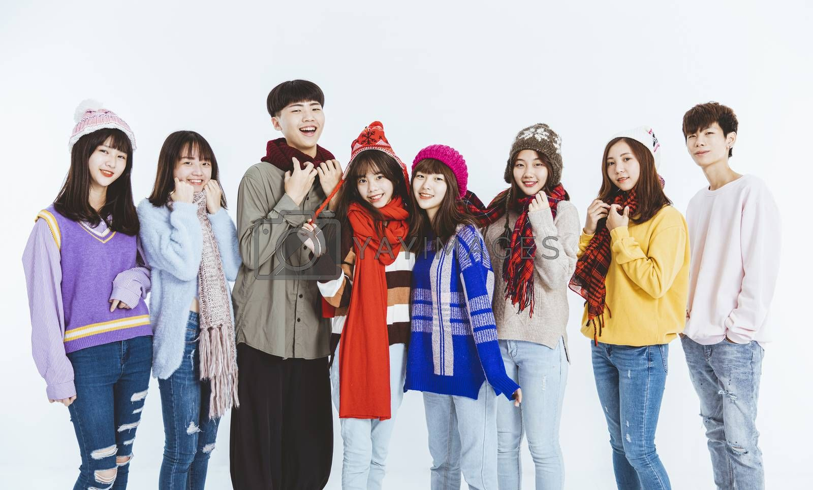 happy young people in winter clothes standing together