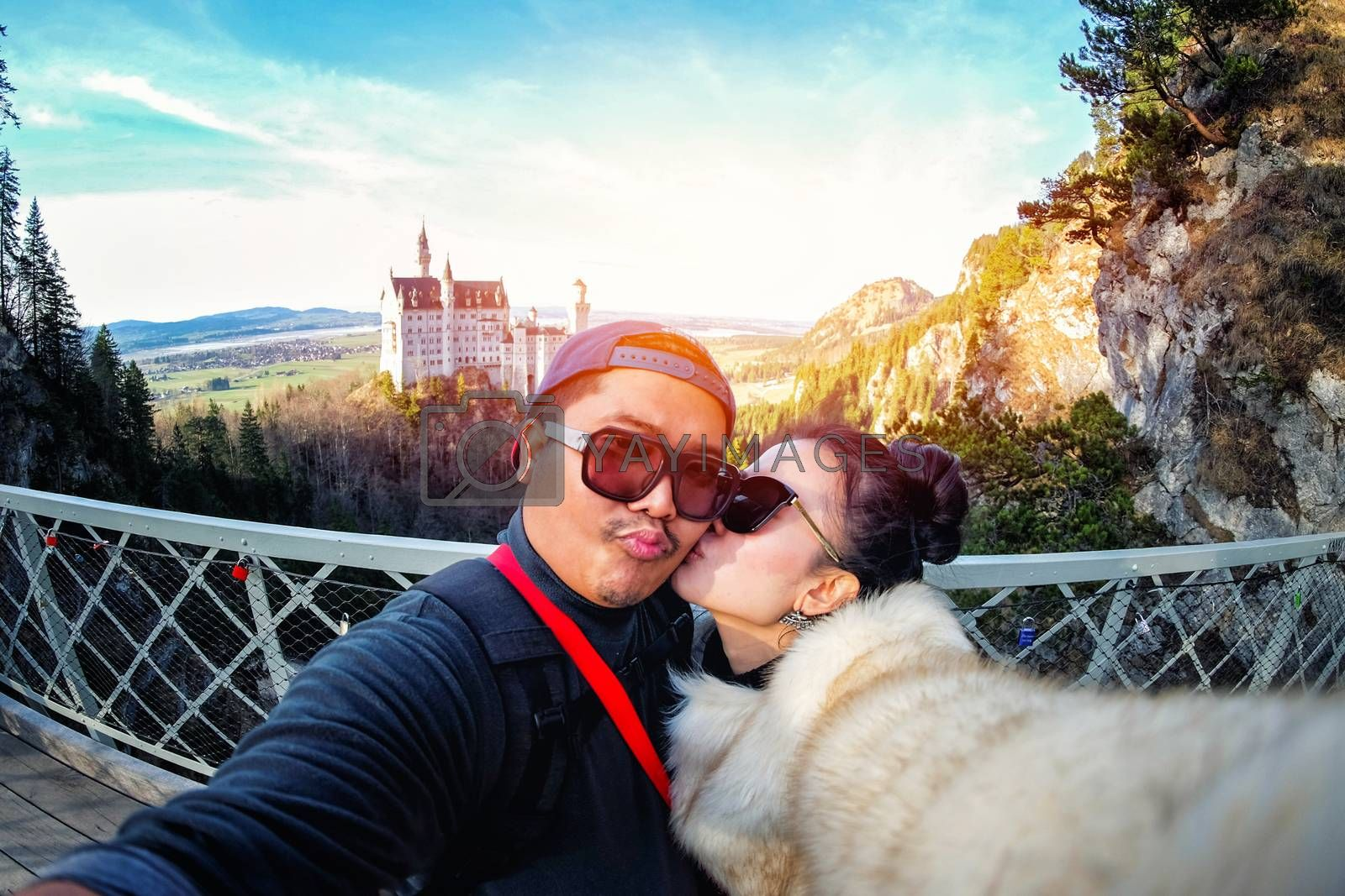 Young Couple Tourists selfie with mobile phone near the Neuschwanstein Castle at daylight in Germany