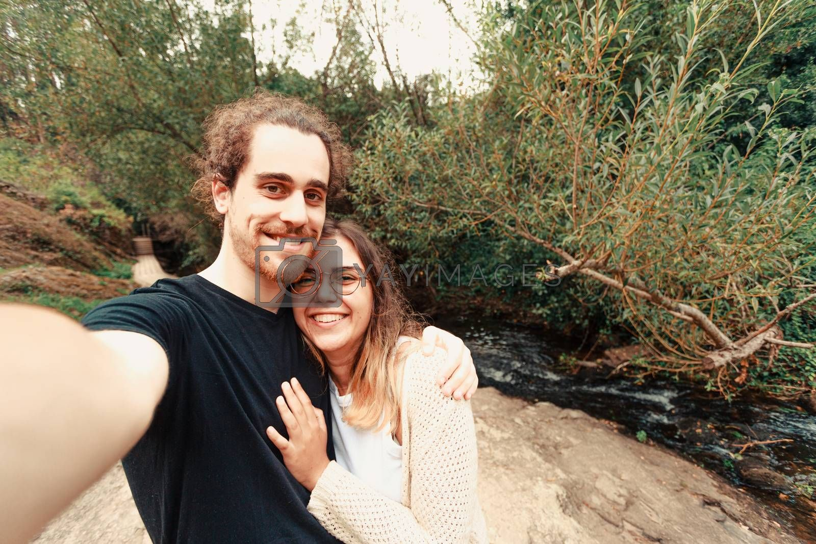 A young couple taking a selfie near a river in Spain