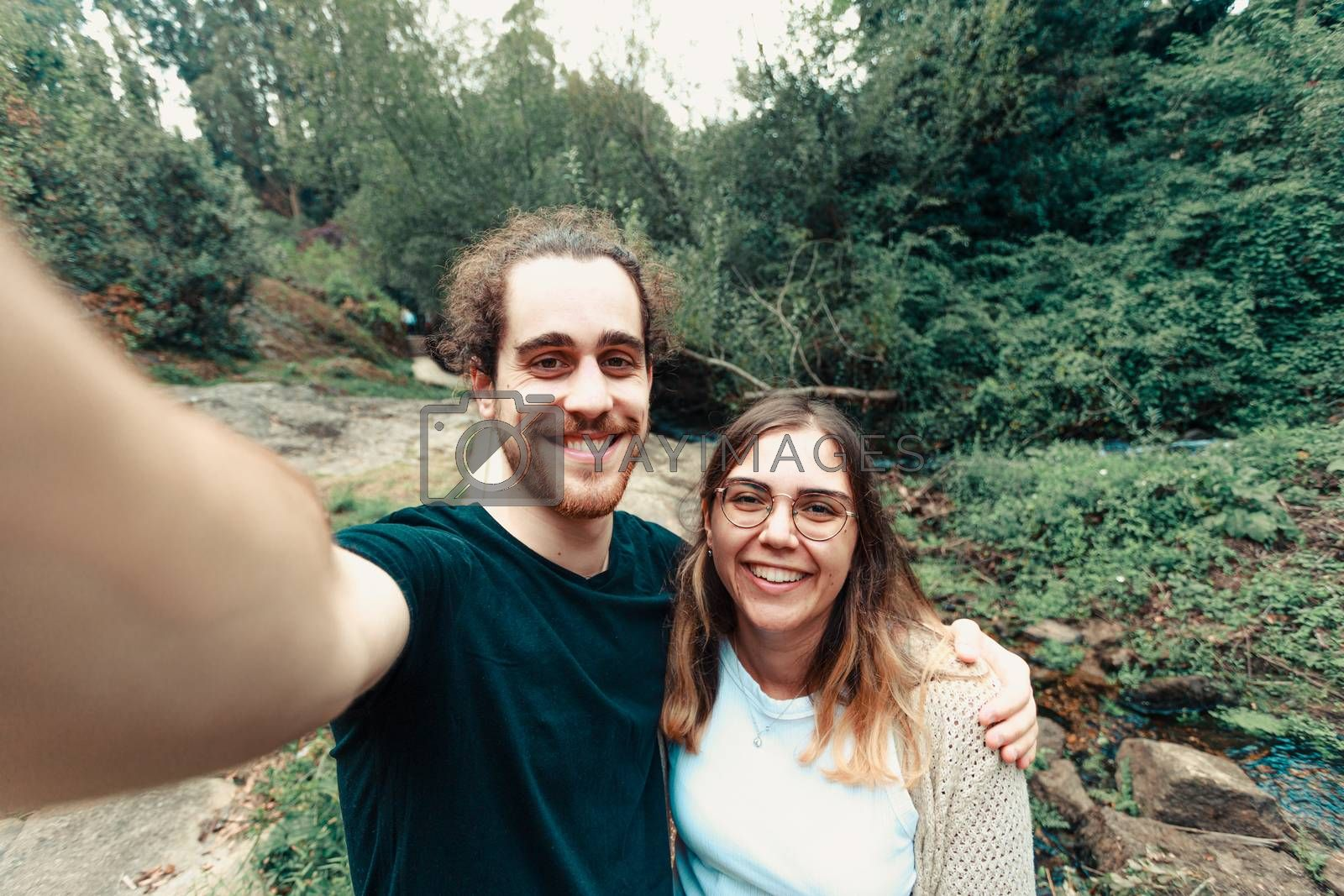 A young couple taking a selfie in the forest while smiling