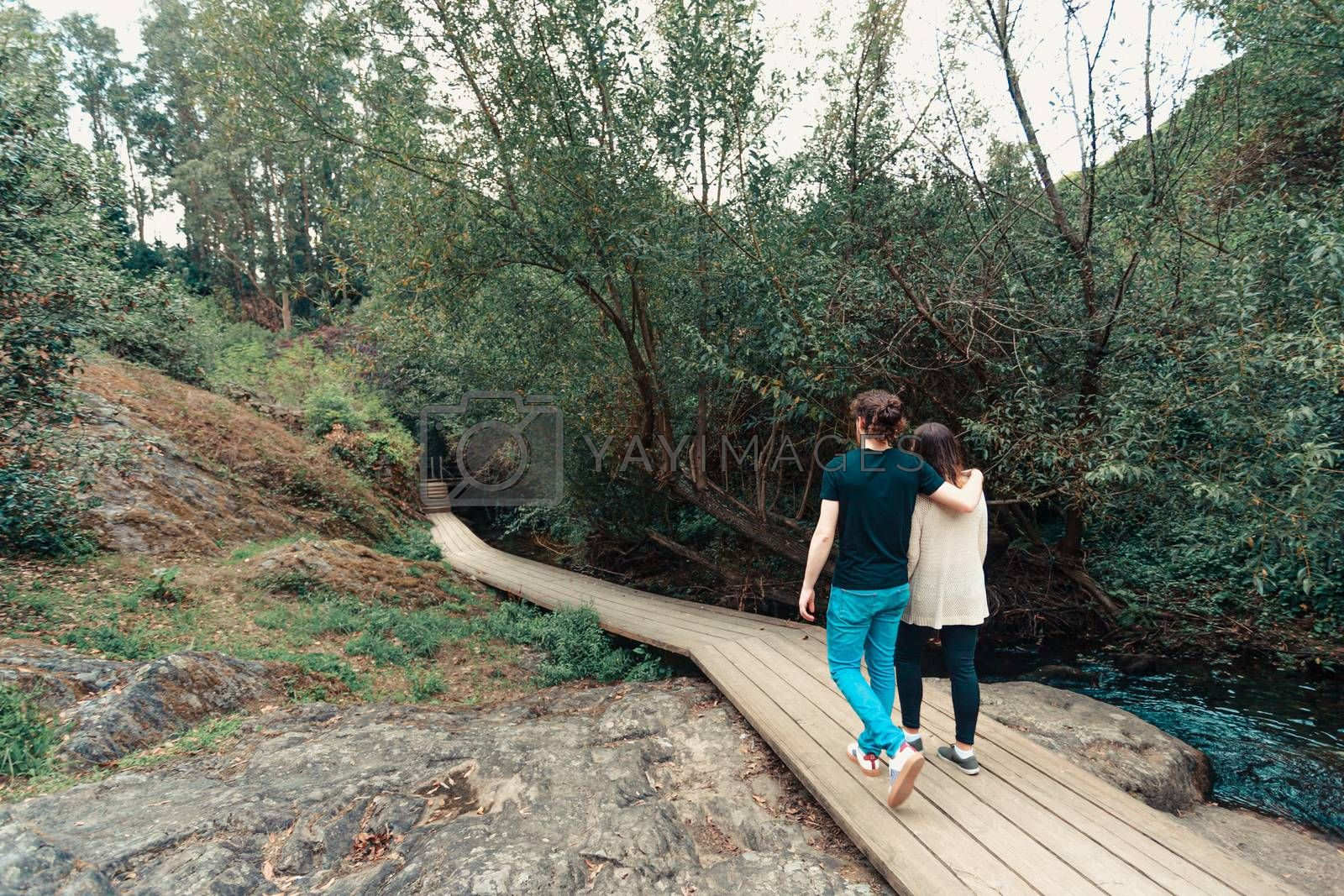 A young couple having a walk by near the river in the forest