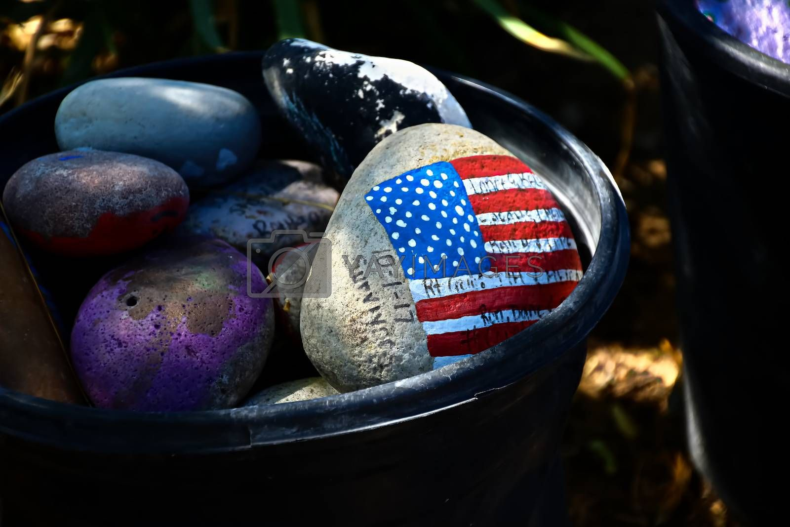 rock painted with the American Flag.American flag painted on a gray stone.Close-up of rock with American flag painted.