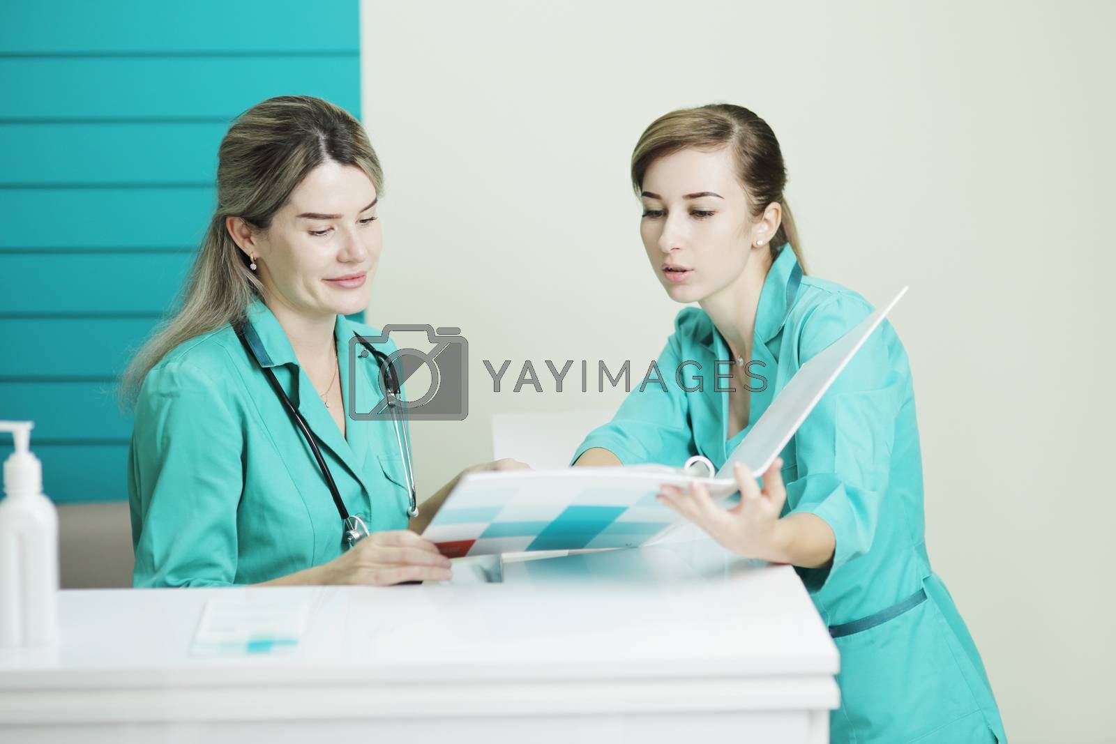 Two female doctor or nurse discussing patient treatment. Stethoscope phonendoscope on the neck. Holds a folder in his hands. Disinfectant on the table