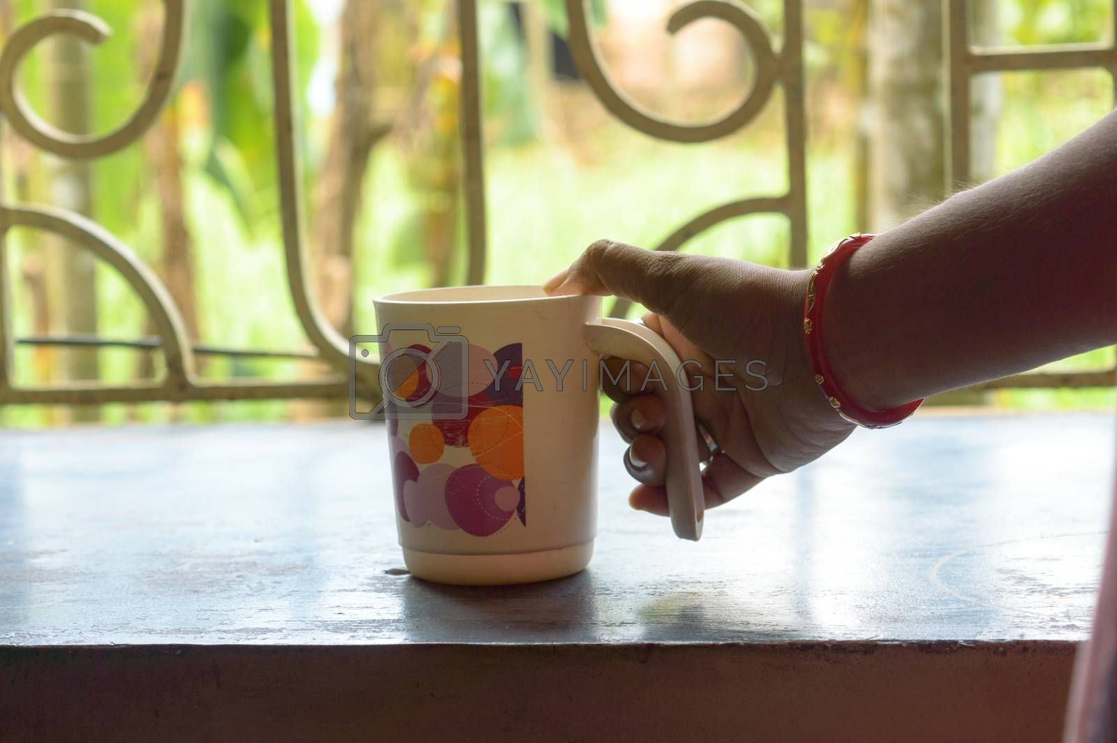 Woman Hand holding coffee cup. Close Up Of Human Hand Holding a Coffee Cup. Female hand hold take away coffee mug At Home. Morning sunny summer day in window sunlight background.