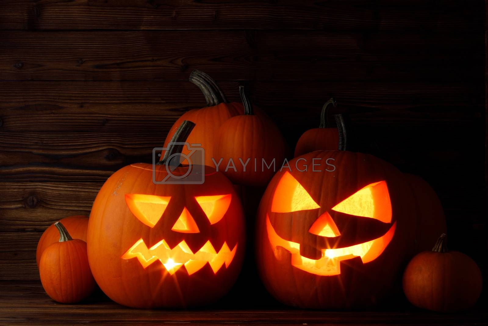 Halloween pumpkin head lanterns and burning candles on wooden background