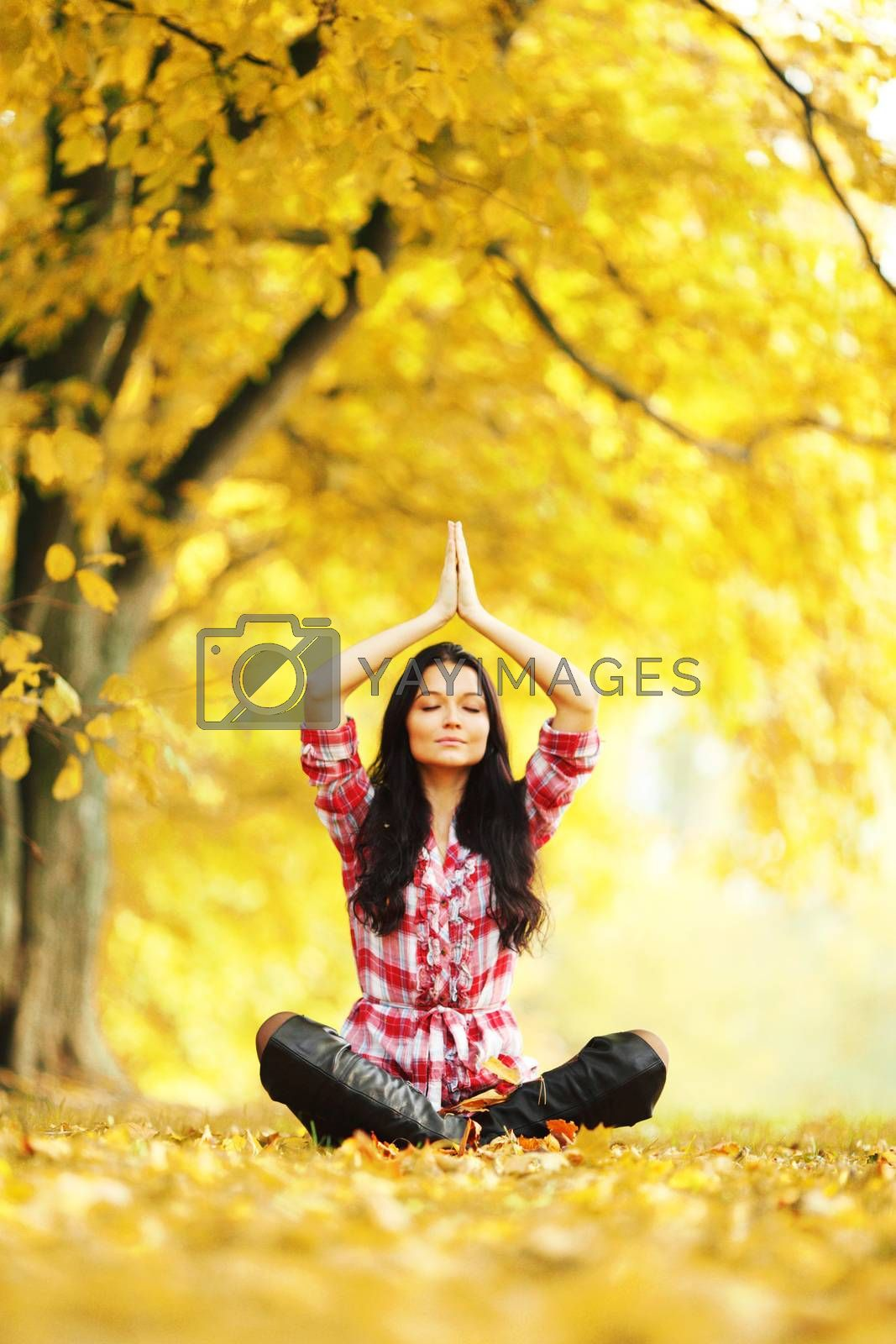 Beautiful young woman sitting in lotus yoga position in autumn park