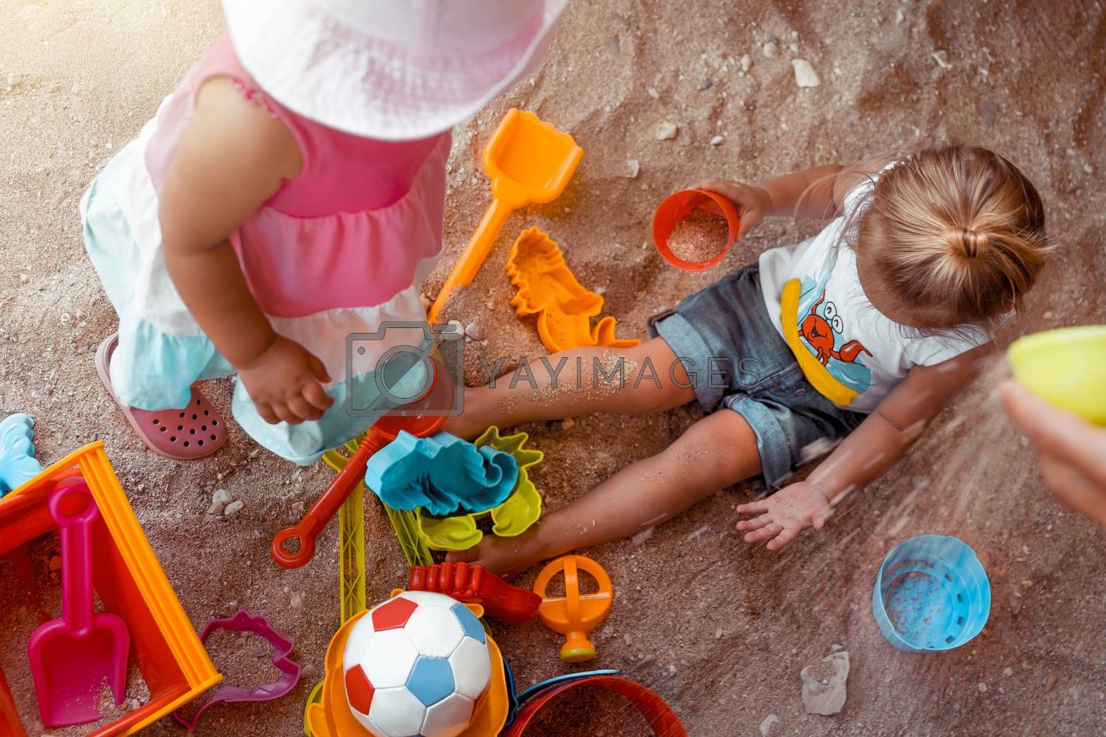 Two Happy Little Kids Playing with Different Colorful Toys in Sandbox. With Pleasure Spending Summer Holidays on the Beach. Enjoying Childhood. Best Friends Forever.