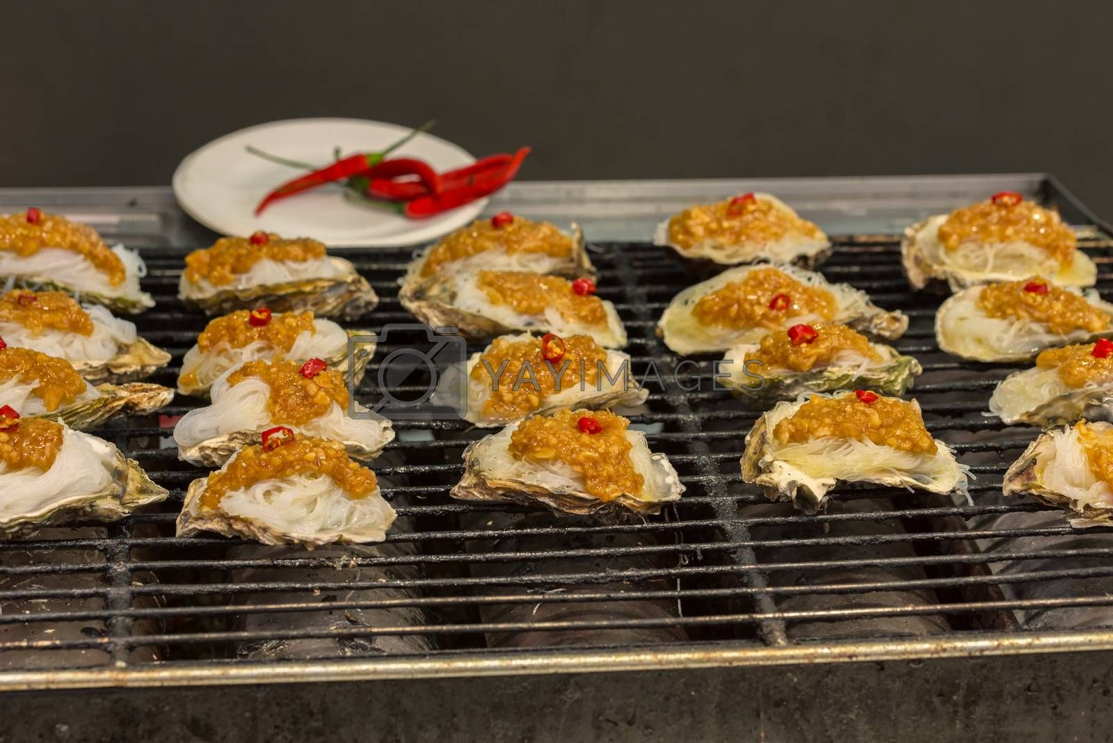 Street food asia. Grilled seafood. Oysters on the grill