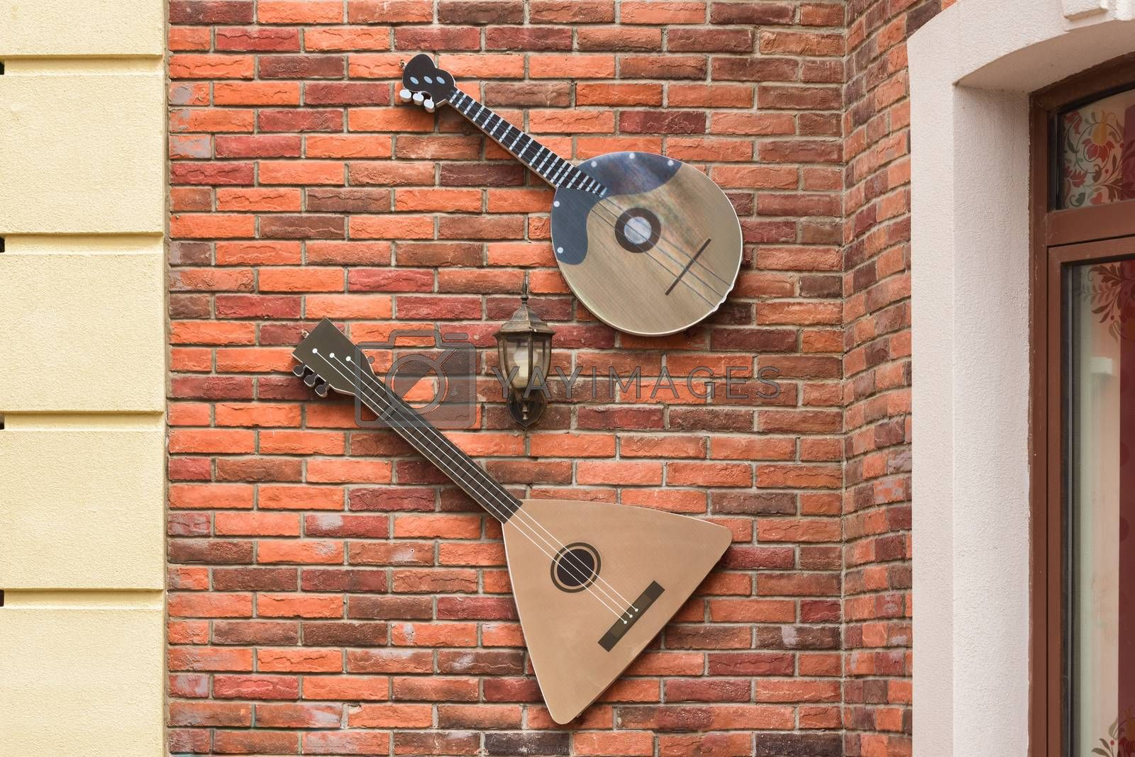 Musical instrument balalaika on the wall. Scenery on the wall of the building