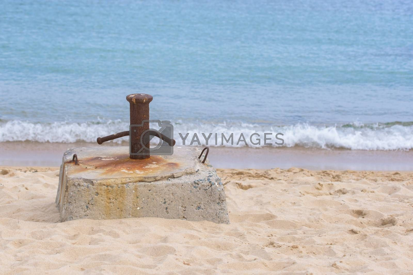 Bollard on the beach. Mooring bollard on sea water background