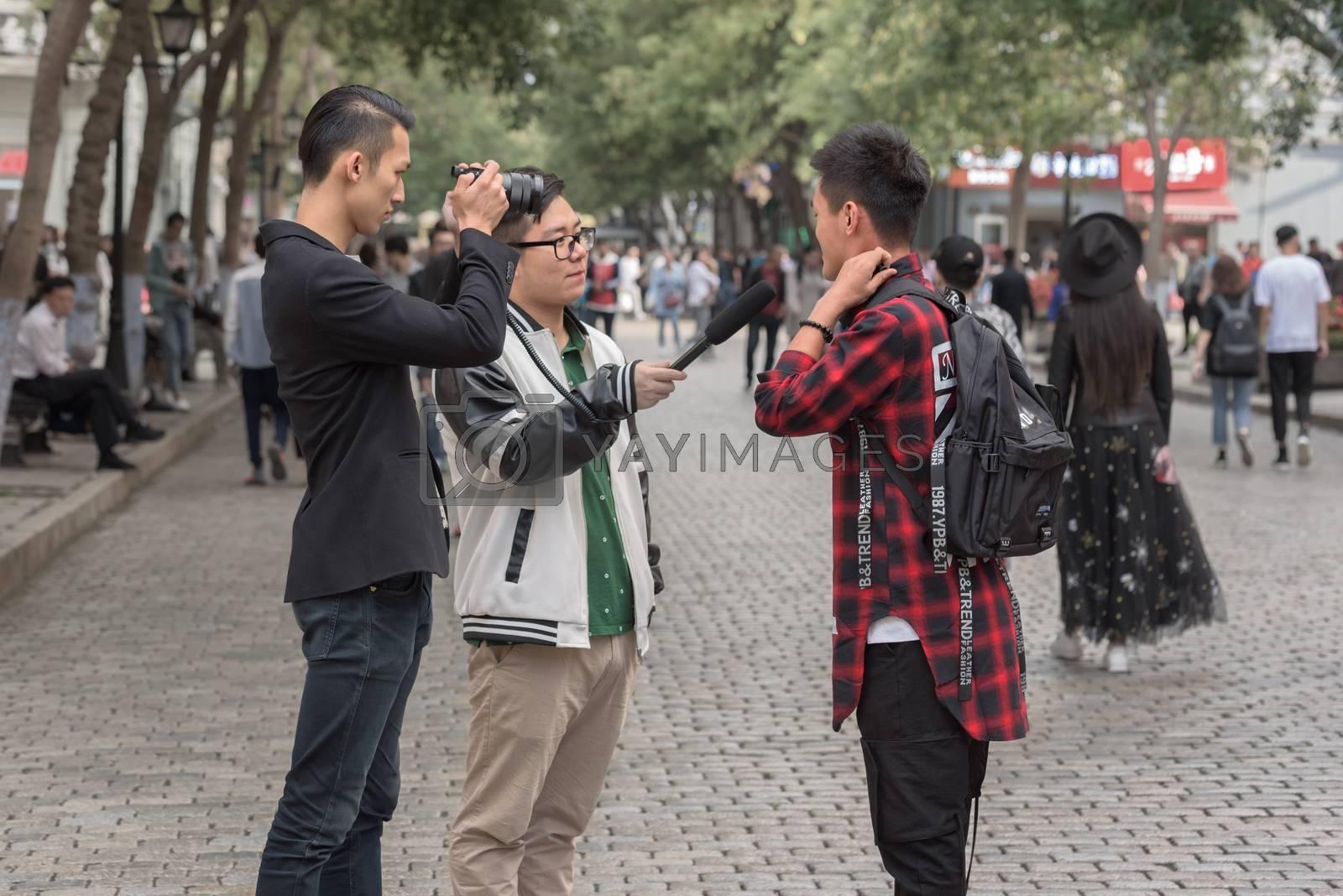 Harbin, Heilongjiang, China - September 2018: Filming interview. Blogger writes video report