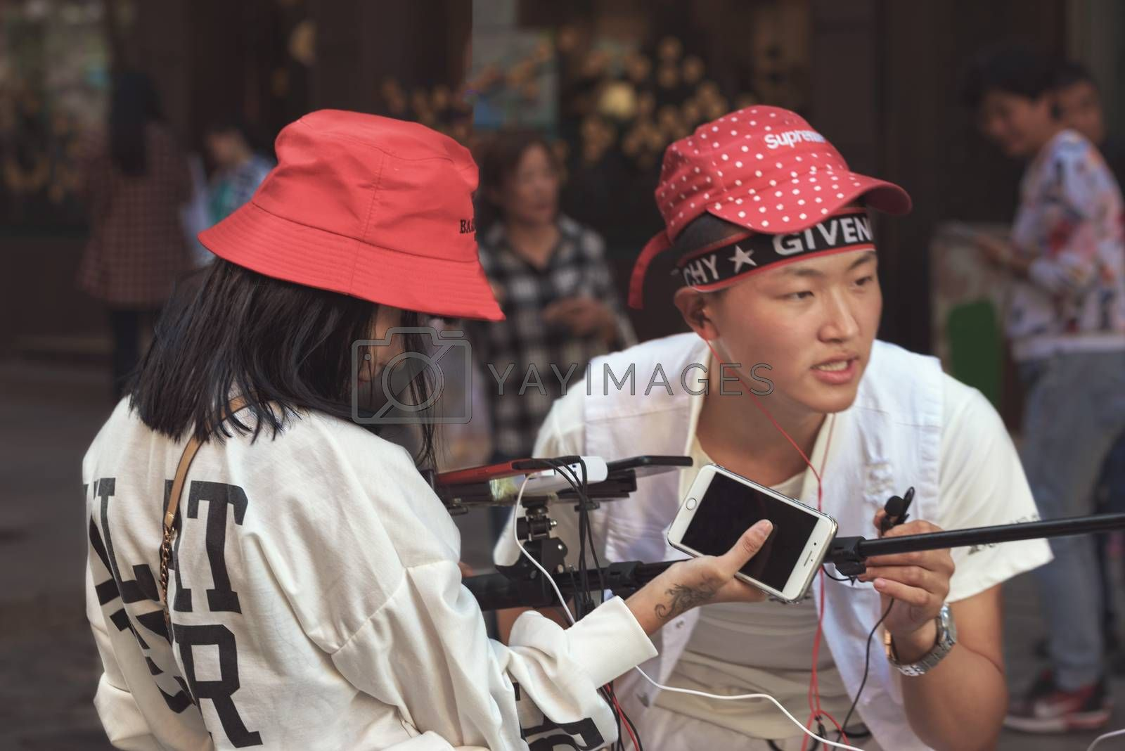Harbin, Heilongjiang, China - September 2018: Young man and woman working as blogger. Blogger writes video report