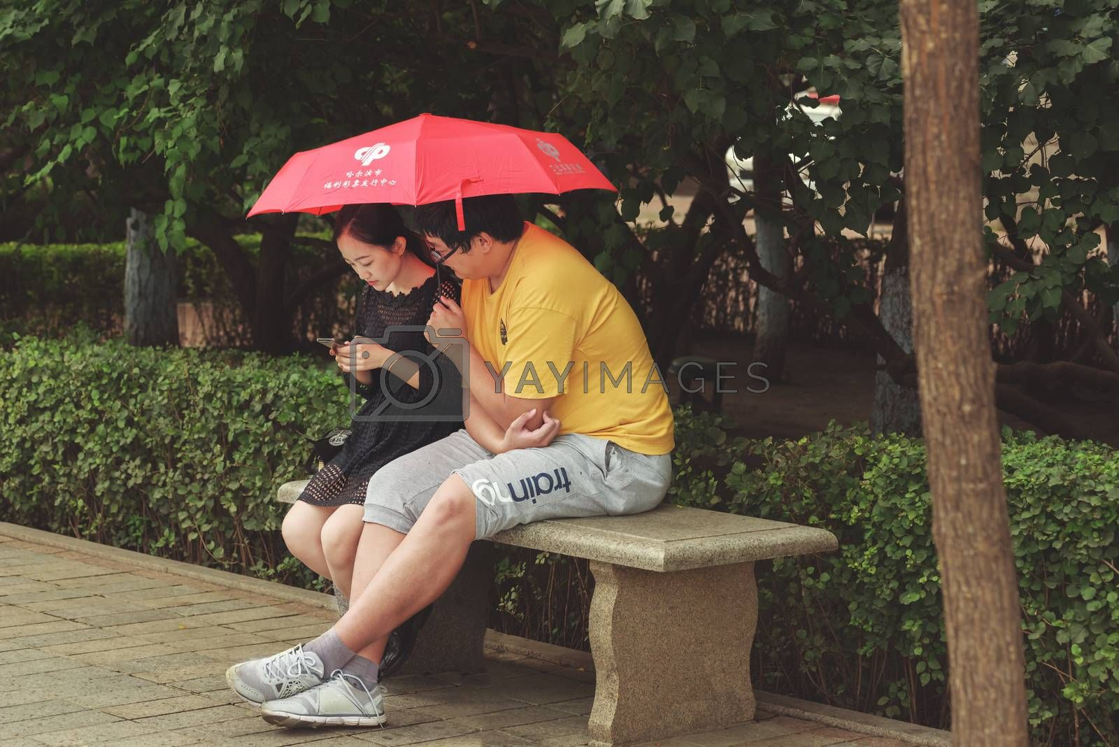 Harbin, Heilongjiang, China - September 2018: Couple sitting on bench. Man and woman under umbrella