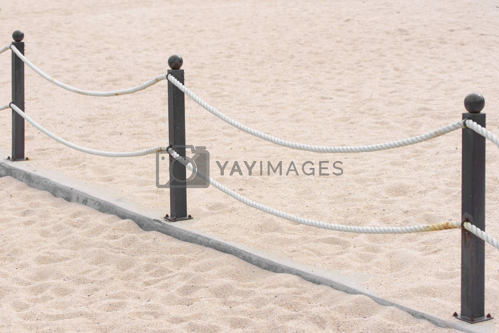 Rope fence on the sandy beach. Prohibition of passage