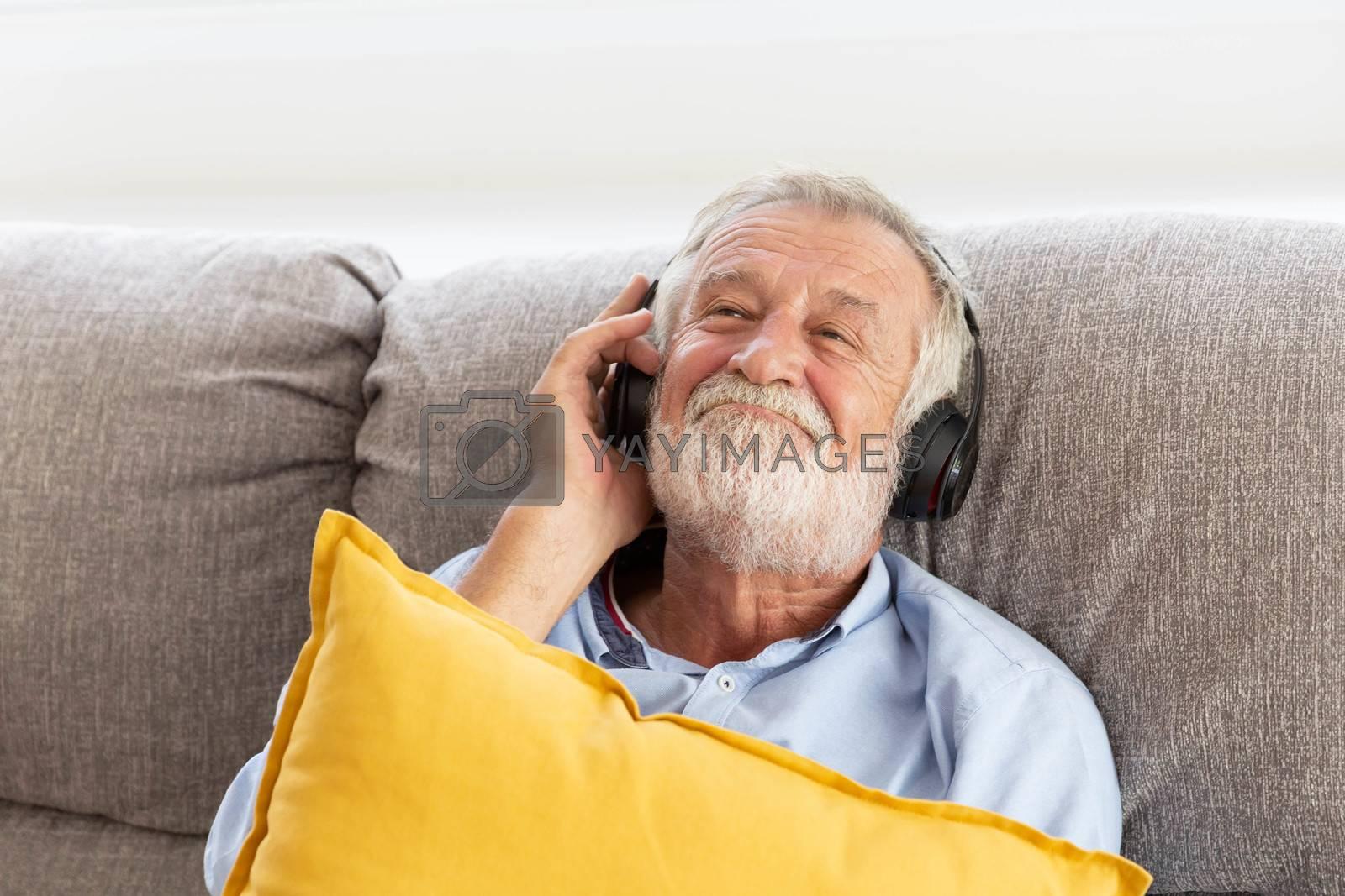 Senior retirement man listen to music using headphone feeling happy in his home