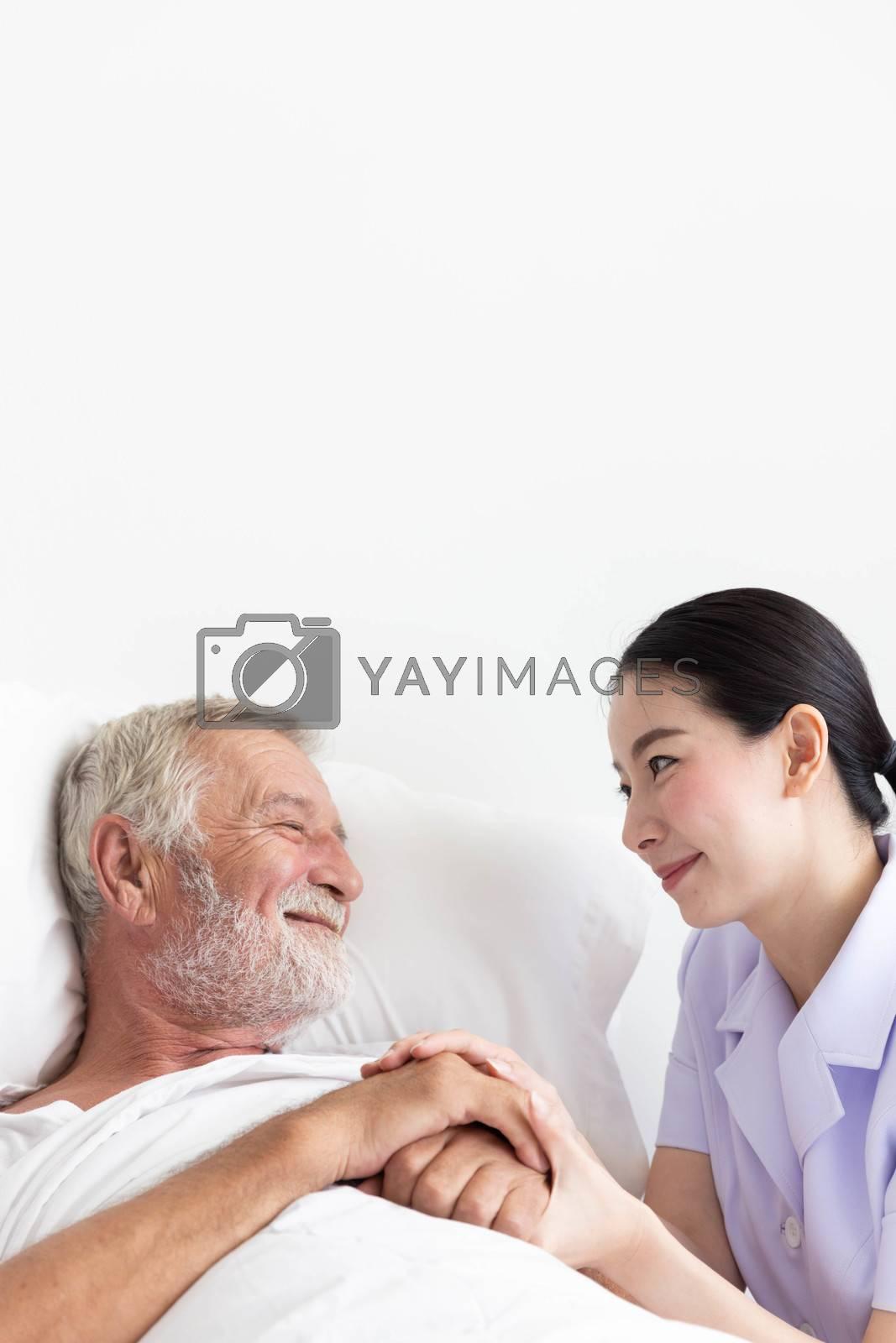 Nurse cares for elderly man lying in bed