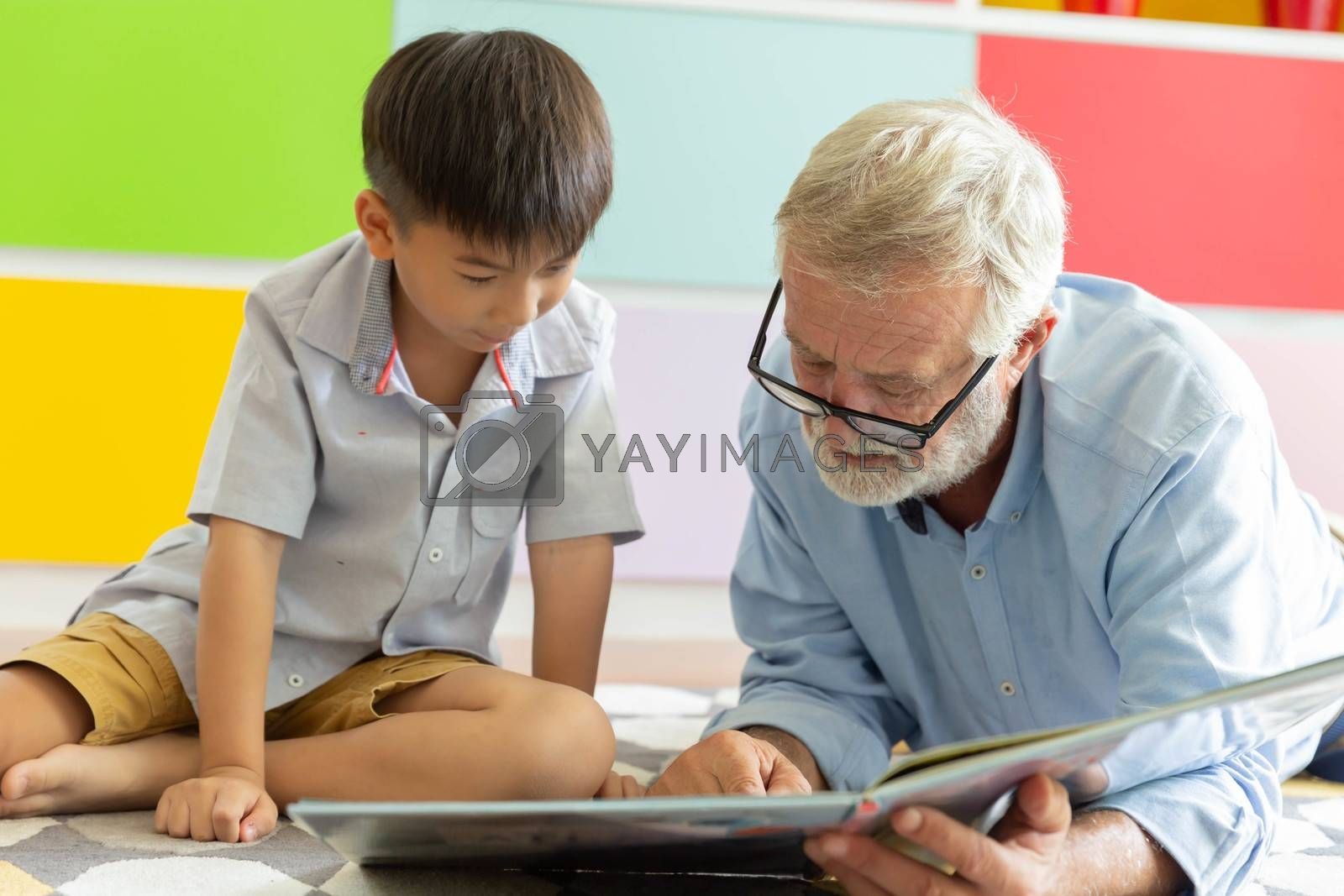 Grandfather and little cute grandson reading book together on the floor in their house
