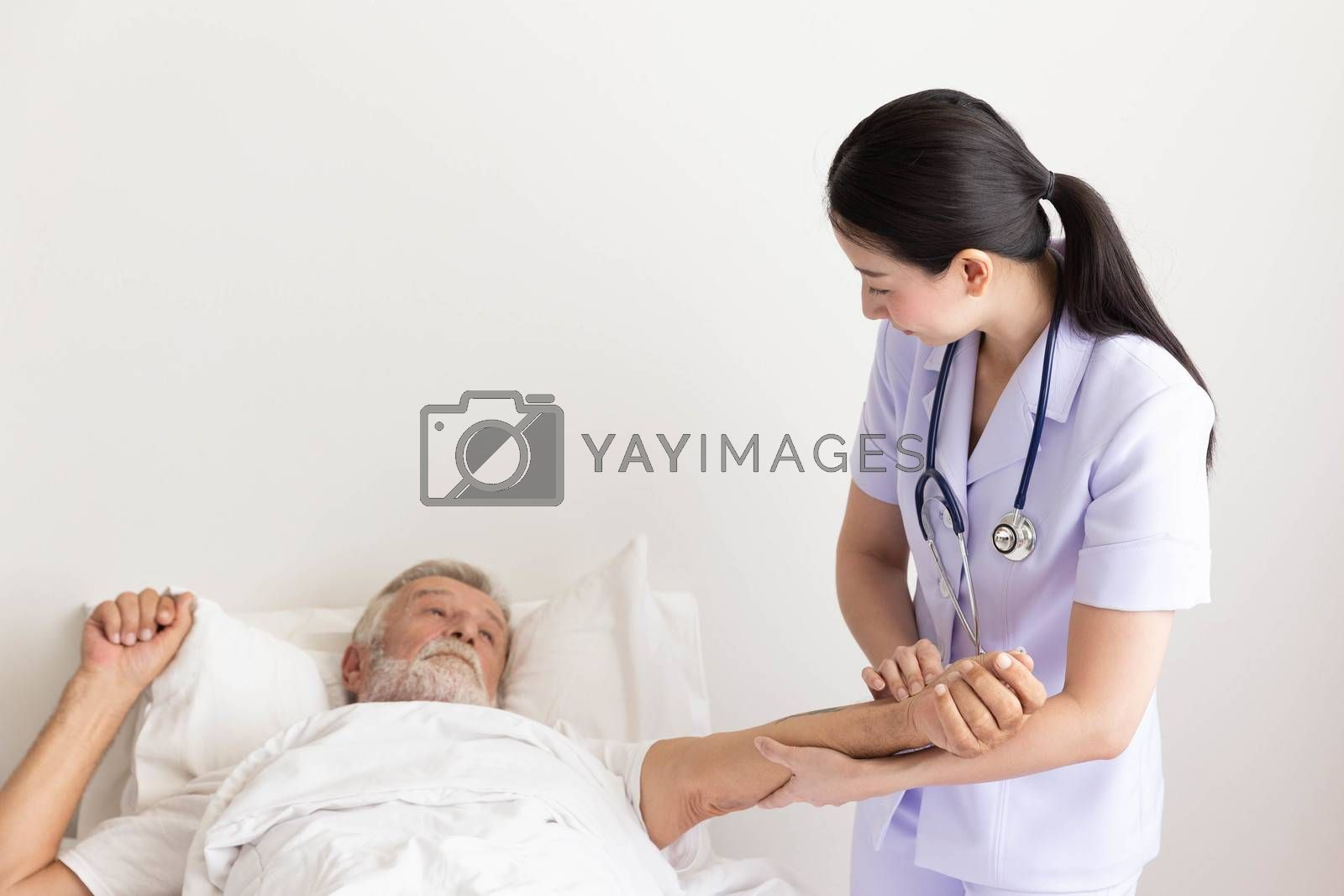 Nurse with stethoscope visiting senior man and checking his heartbeat on his bed