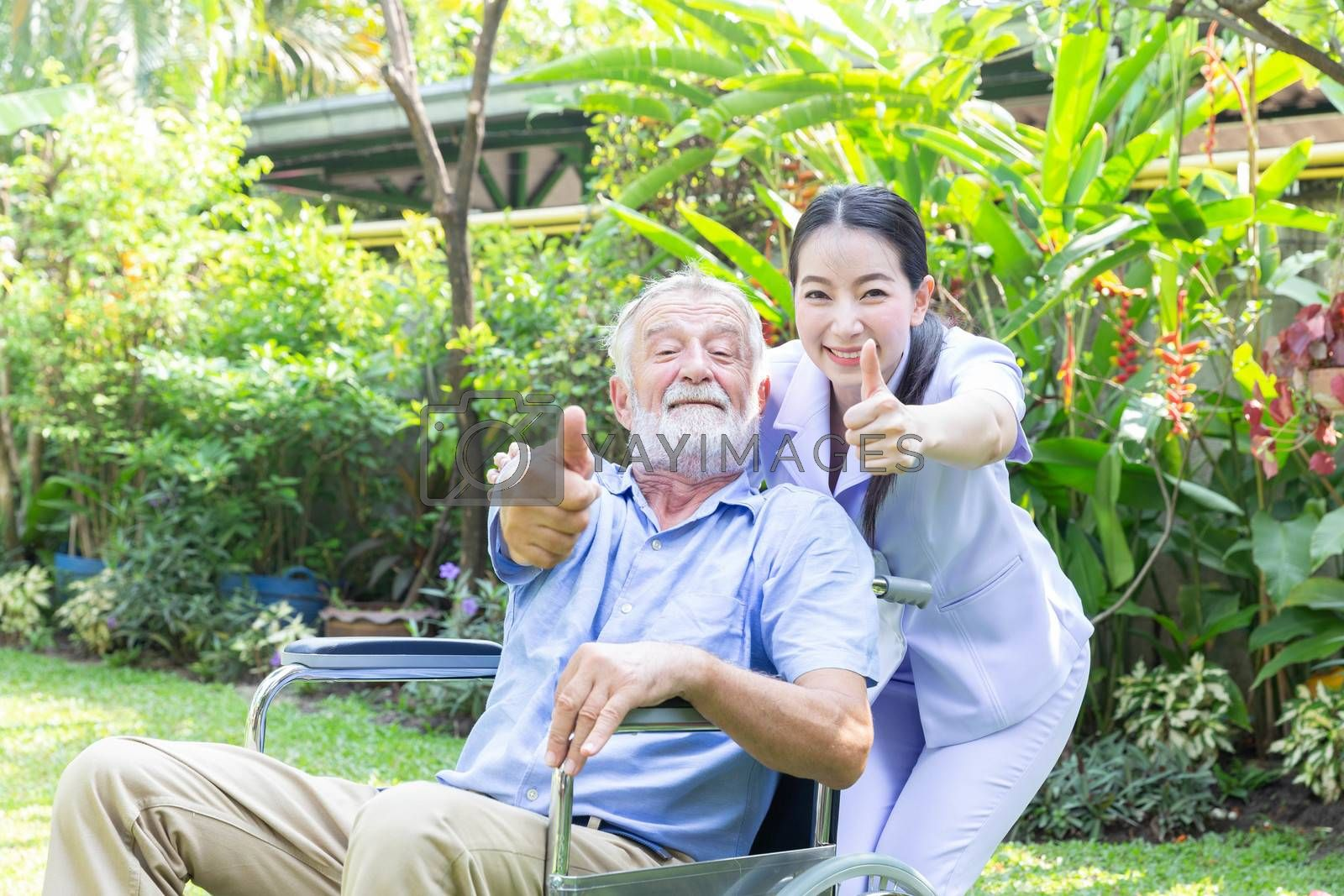 A nurse take care a senior male and thumb up on wheelchair in his garden at home