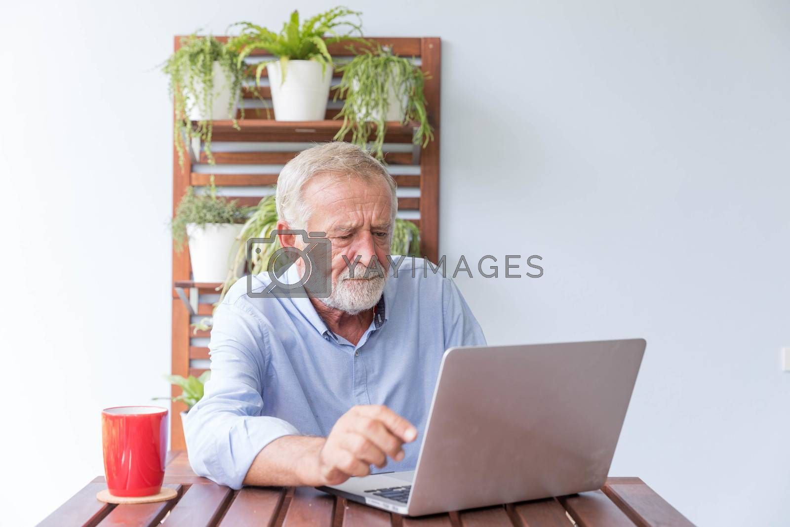 Senior retirement man is working with his laptop at home feeling