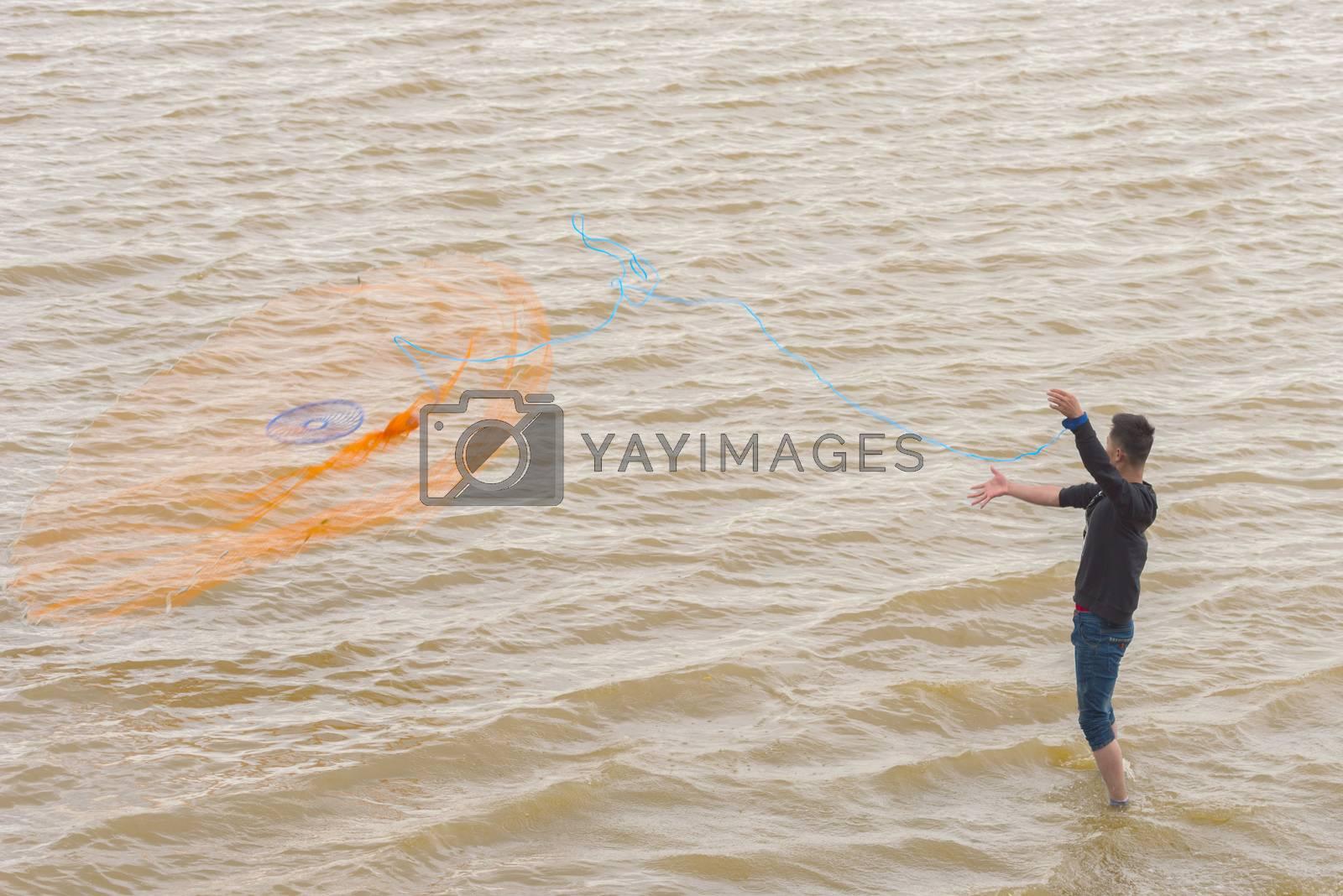Asian fisherman casting a net for catching freshwater fish. Fisherman on the river. Fishing on the lake. Fishing net