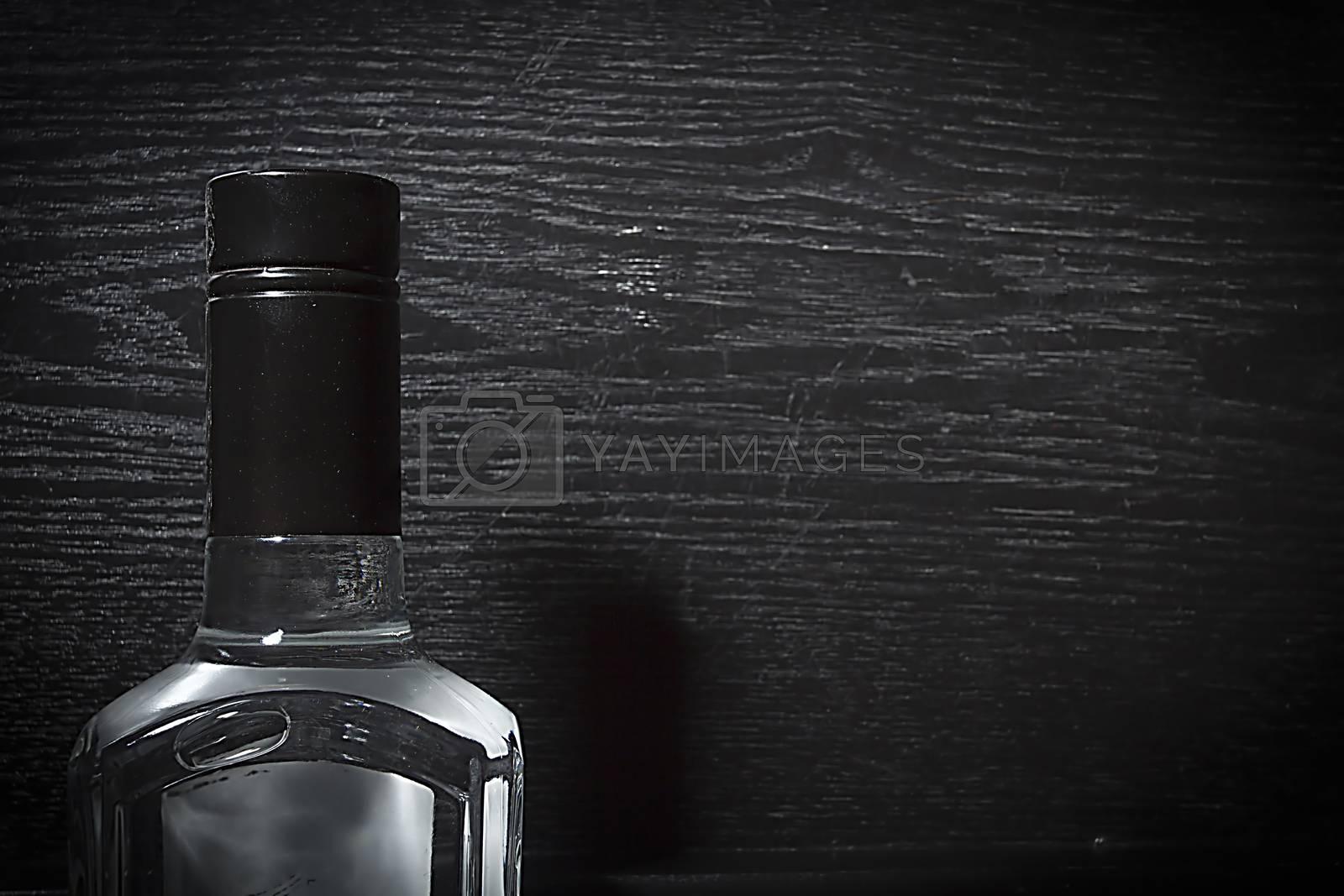 Neck of bottle with vodka on black wooden background