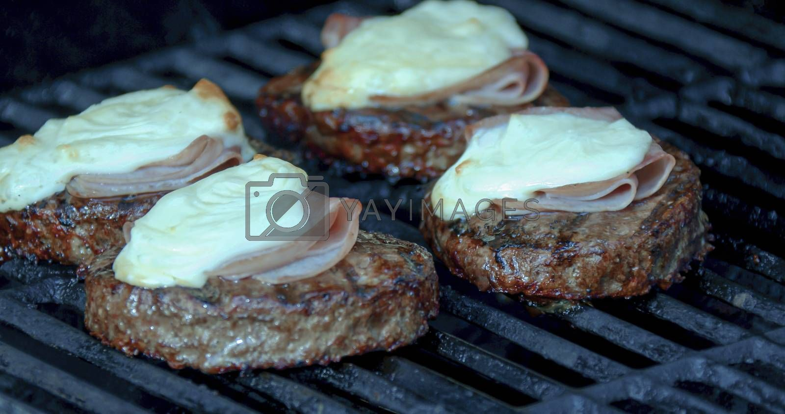 Cooking a burger patty with melted cheese and ham on a grill
