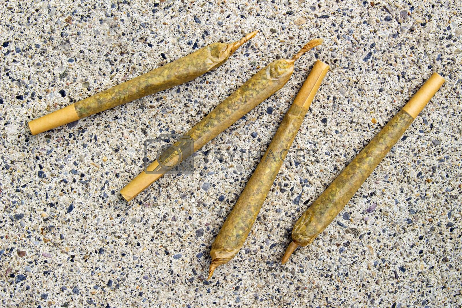 Cannabis Pre-Roll Joints Cigarettes on a concrete texture.