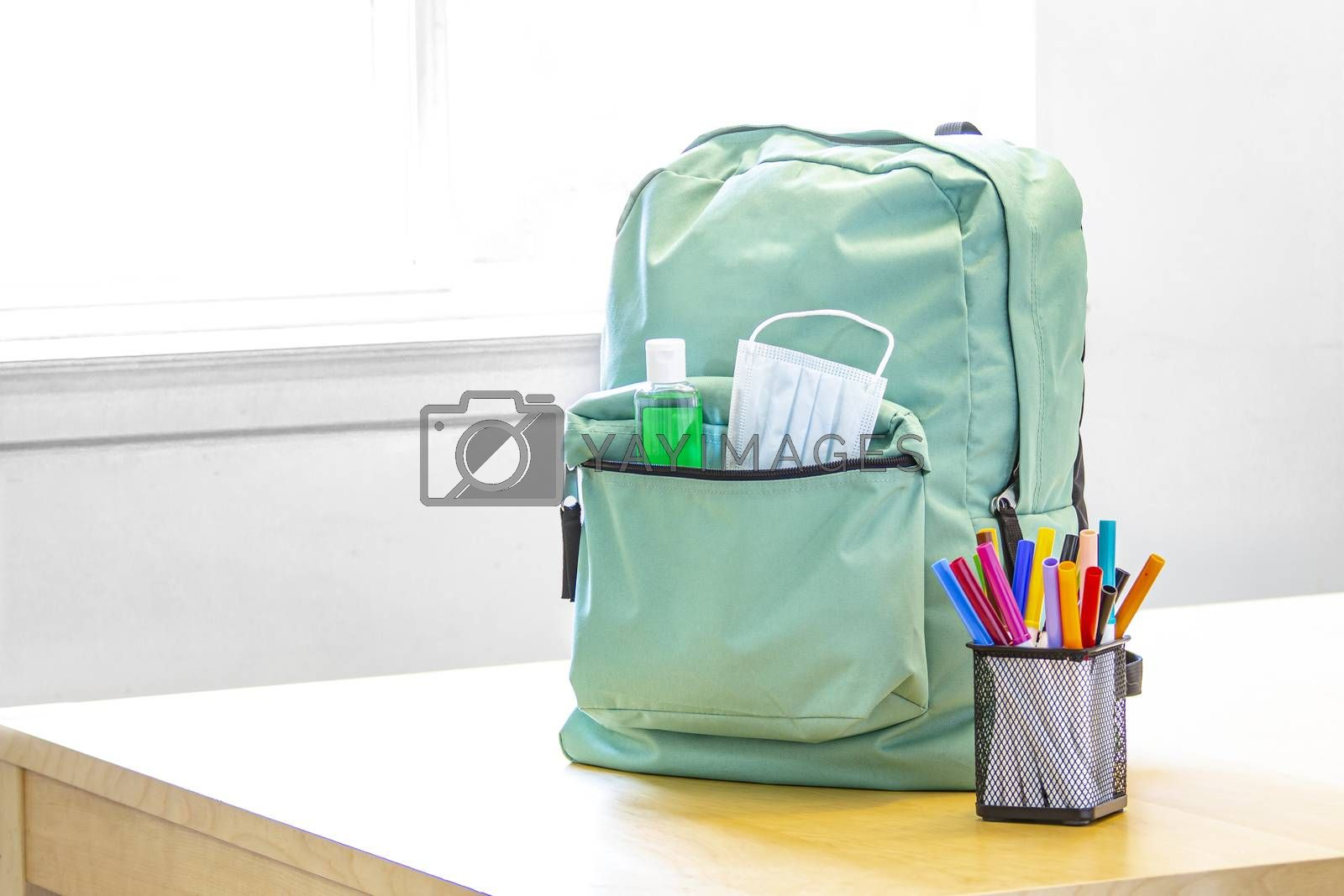 A student school bag pack with sanitizer and a face mask and pencil markers on a table. Back to school during global pandemic. Covid 19.
