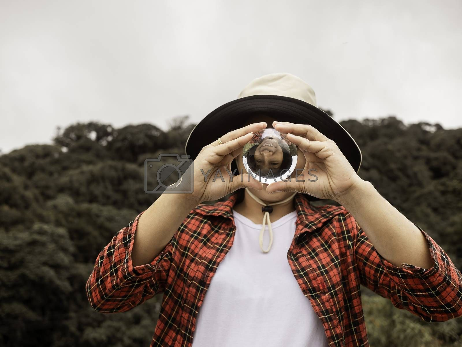 Asian woman  holding and look into a magic crystal glass ball on nature background.