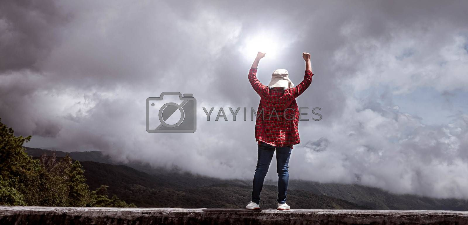 Female standing with success with fists raised up on peak of mountain with sky background.  Achievement and winning concept.