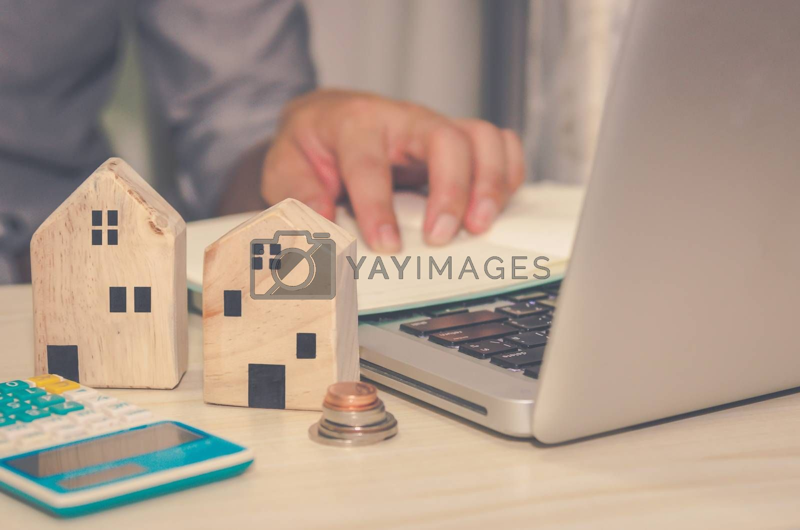 A small wooden house on the desk A man  laptop computer and calculator Real estate business concept Property insurance.