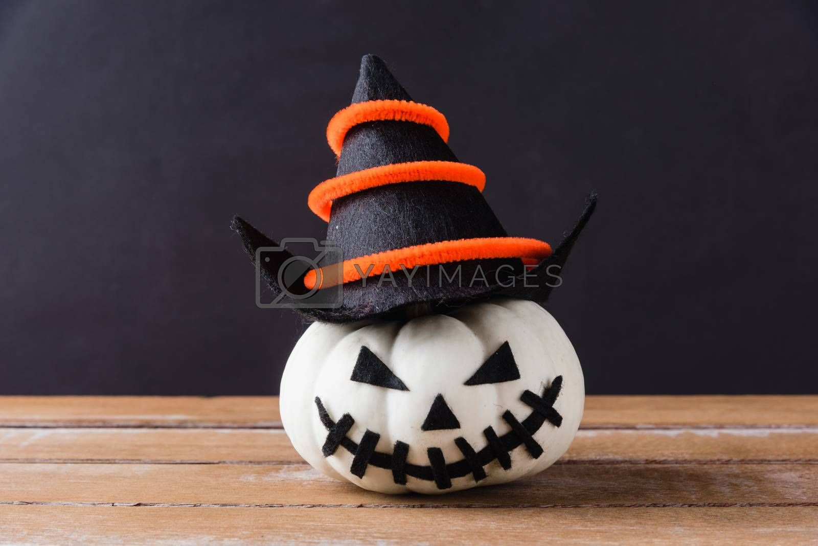 Funny Halloween day party concept ghost pumpkins head jack lantern scary smile wear hat on wooden table and black background, studio shot isolated, Holiday decoration