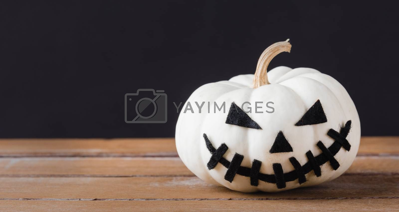 Funny Halloween day party concept ghost pumpkins head jack lantern scary smile on wooden table and black background, studio shot isolated, Holiday decoration
