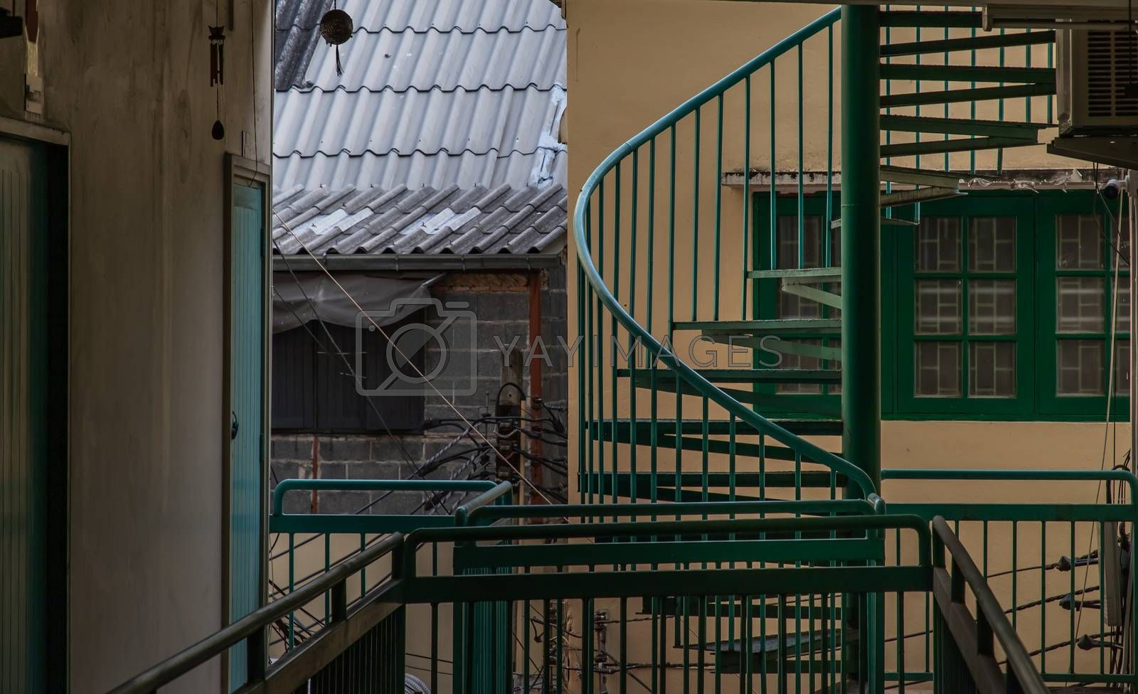 Bangkok, Thailand - 25 Jan 2020 : Green spiral staircase pattern in old apartment. Spiral stairs circle in courtyard architecture. Outdoor ladder decoration interior. Selective focus.