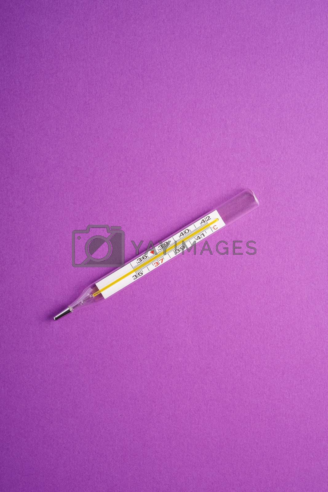 Analog thermometer on violet purple background, healthcare medical concept, antibiotics and cure, top view copy space