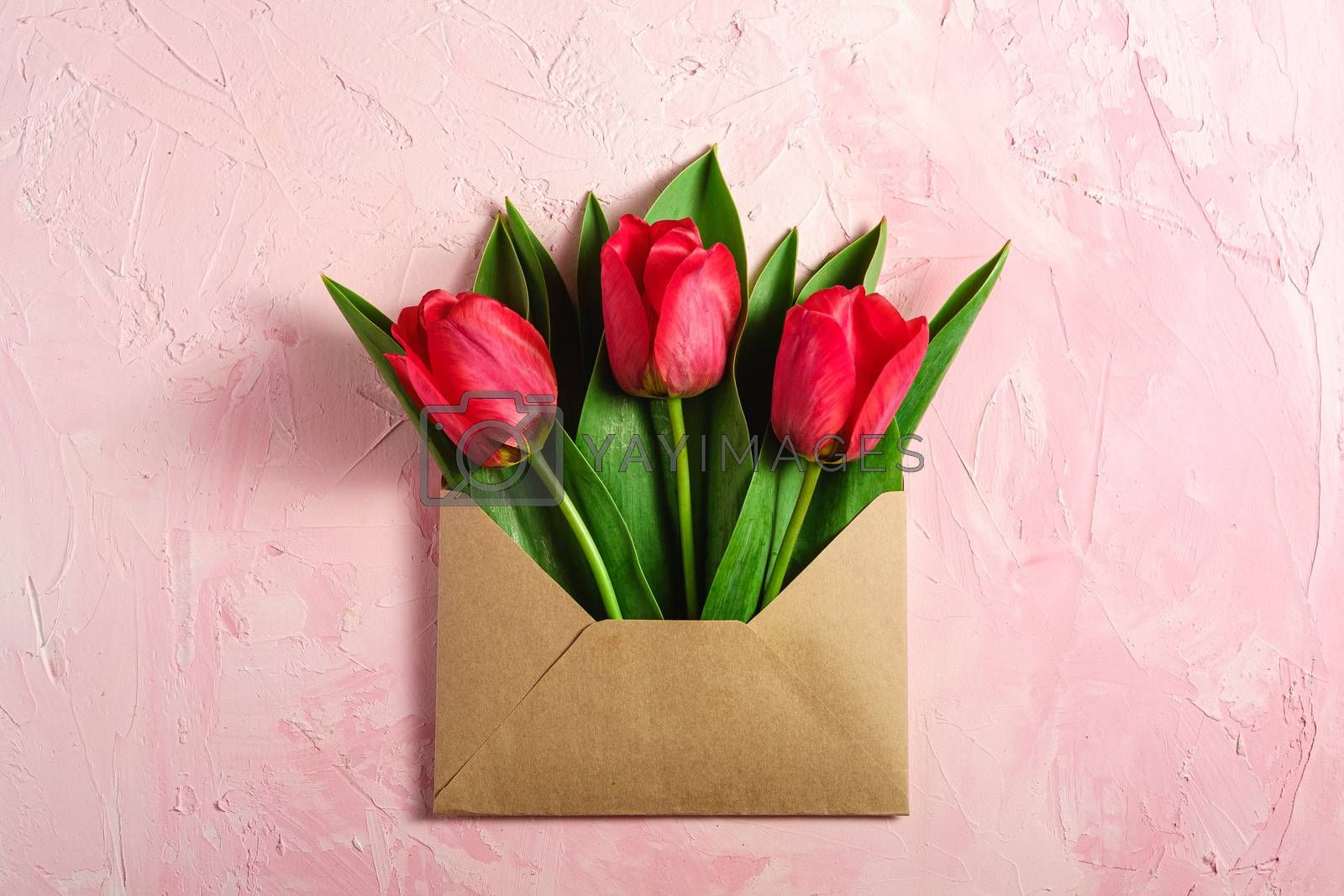 Bunch of red tulip flowers in paper envelope on textured pink background, top view copy space