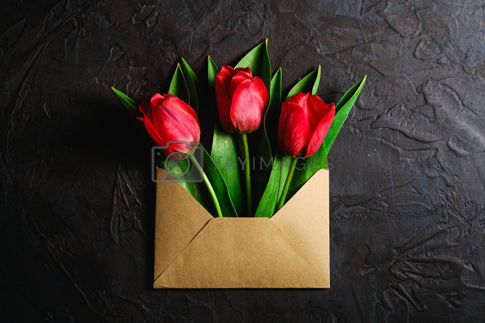 Bunch of red tulip flowers in paper envelope on textured dark black background, top view copy space