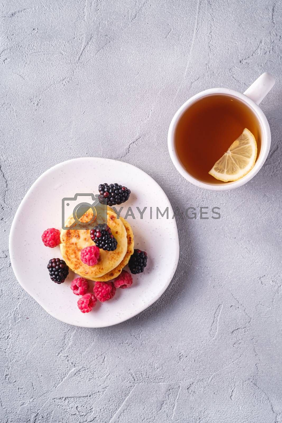Cottage cheese pancakes, curd fritters dessert with raspberry and blackberry berries in plate near to hot tea cup with lemon slice on stone concrete background, top view