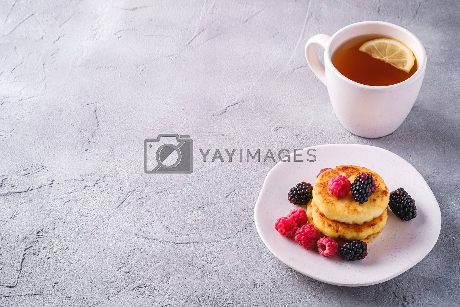 Cottage cheese pancakes, curd fritters dessert with raspberry and blackberry berries in plate near to hot tea cup with lemon slice on stone concrete background, angle view copy space