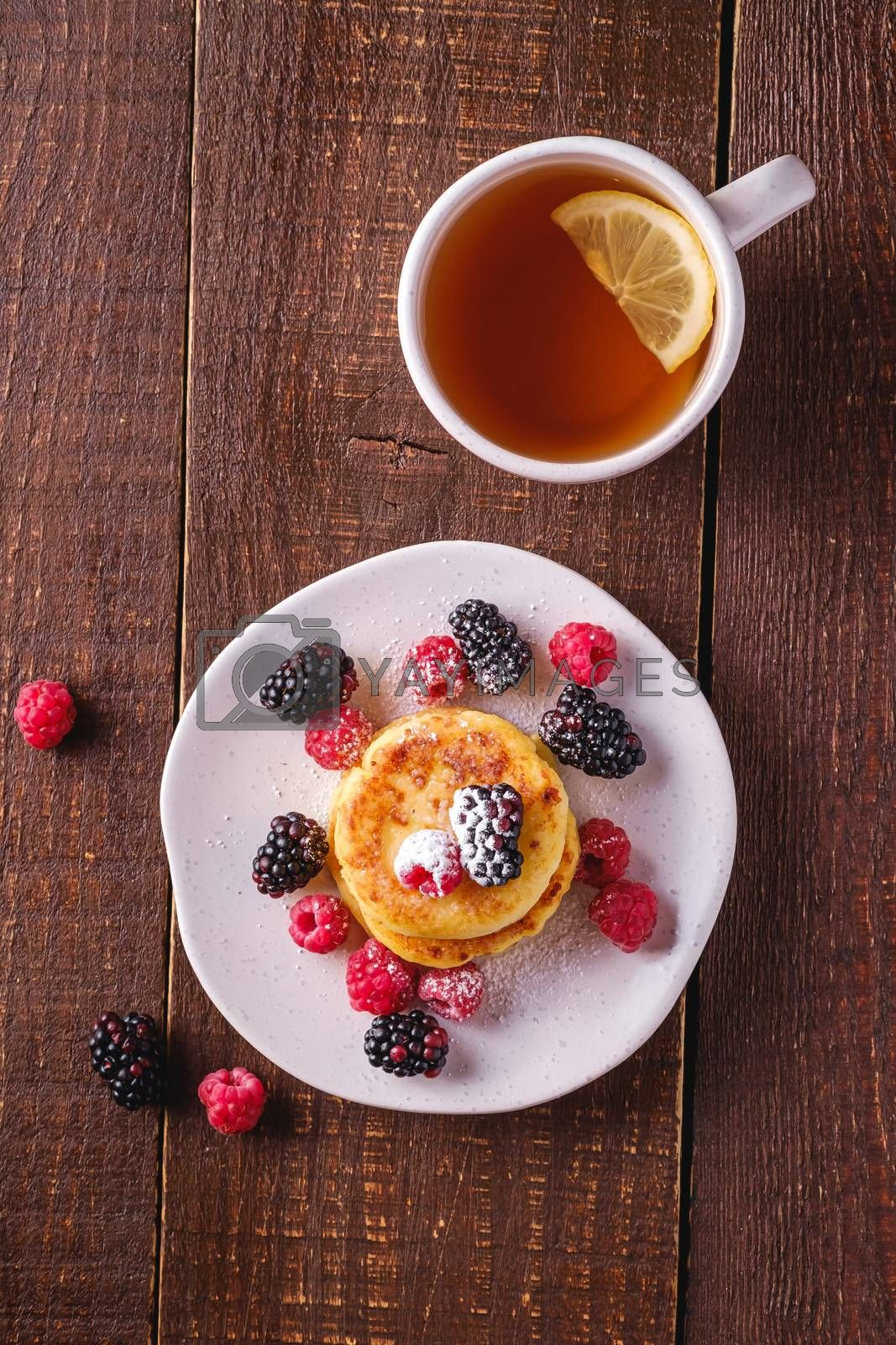 Cottage cheese pancakes, curd fritters dessert with raspberry and blackberry berries in plate near to hot tea cup with lemon slice on dark brown wooden background, top view
