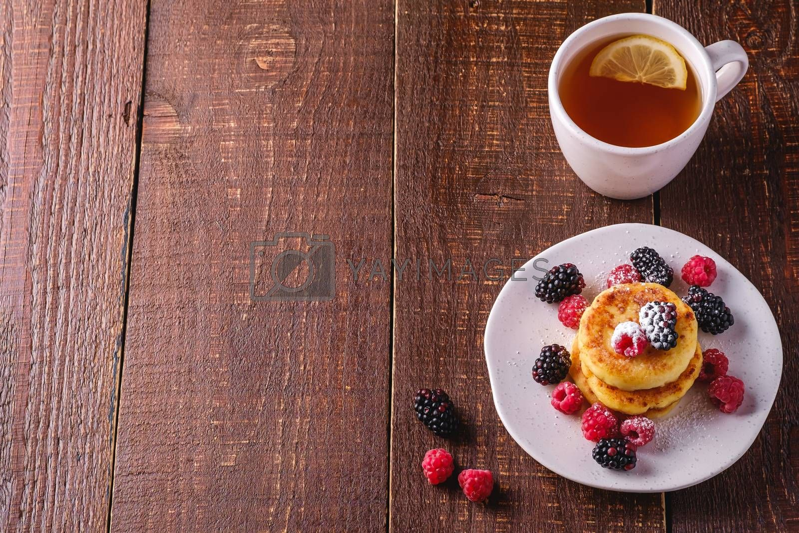 Cottage cheese pancakes, curd fritters dessert with raspberry and blackberry berries in plate near to hot tea cup with lemon slice on dark brown wooden background, angle view copy space