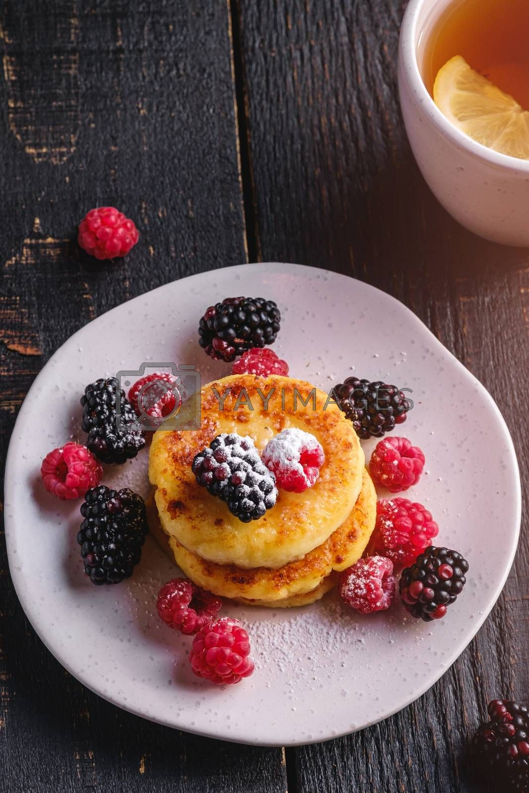 Cottage cheese pancakes, curd fritters dessert with raspberry and blackberry berries in plate near to hot tea cup with lemon slice on dark black wooden background, angle view