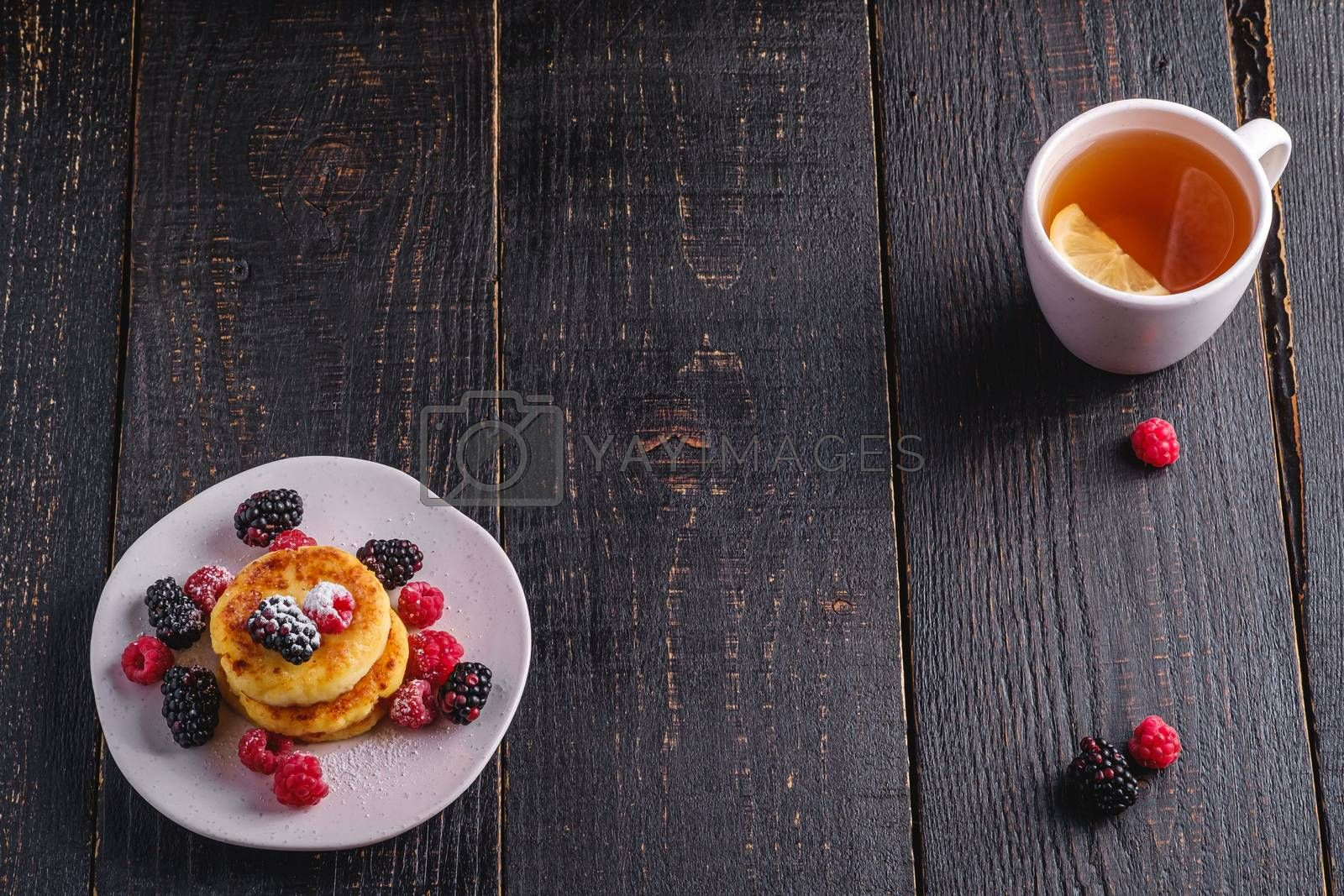 Cottage cheese pancakes, curd fritters dessert with raspberry and blackberry berries in plate near to hot tea cup with lemon slice on dark black wooden background, angle view copy space