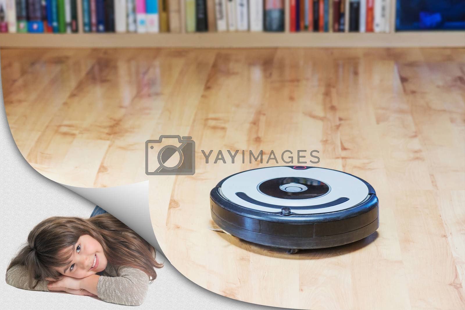Using the robotic vacuum cleaner to clean the floor. Smiling cute little girl is lying in an exposed corner looking at the camera. All potential trademarks and control buttons are removed.